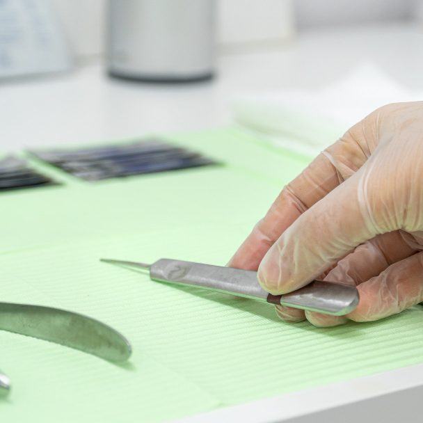 closeup-podiatrists-hand-wearing-gloves-taking-gouge-from-work-table (1)